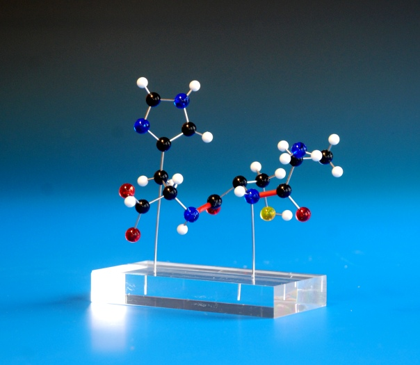 A molecular model of a simple metal coordination compound on a clear acrylic base
