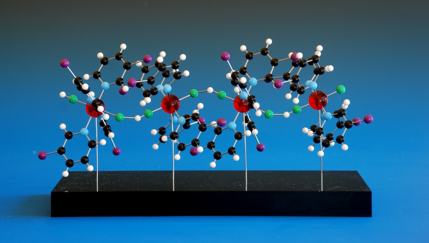 A ball and stick model of a polymeric coordination compound on a black acrylic base